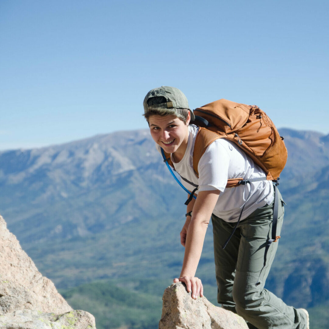 Young woman climbs to the top of a mountain