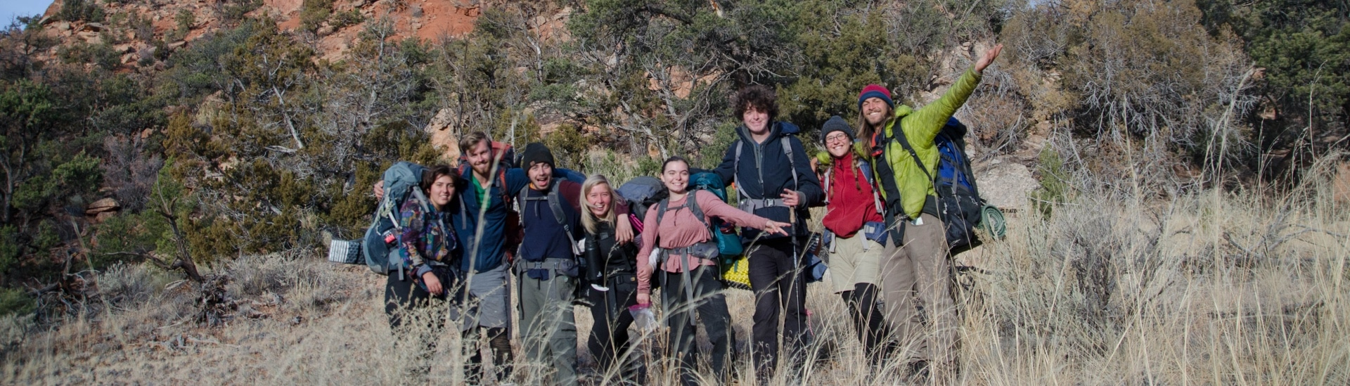 group of young people with backpacks on smiling in nature