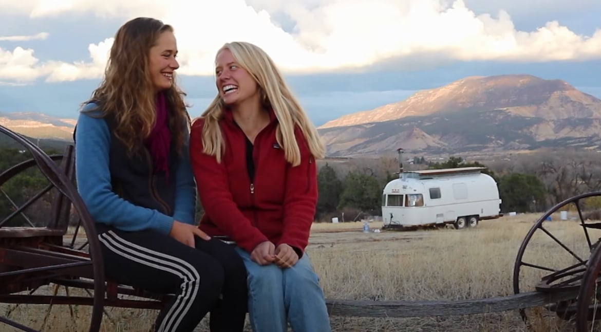 Two young women talking about their gap year experience with mountains in the background.