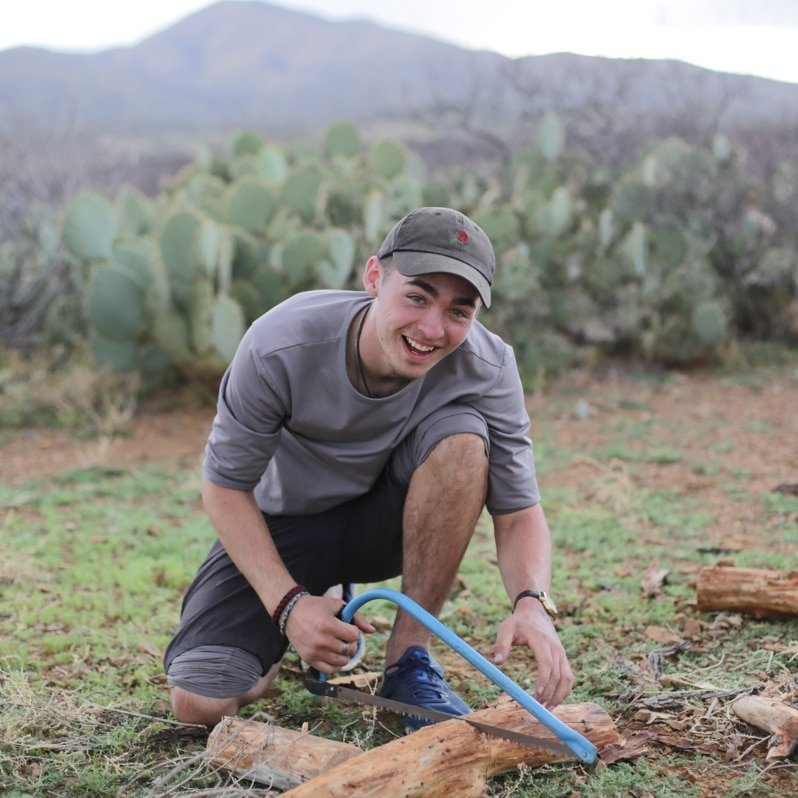 A young man practicing outdoor skills saws a log in the desert with a hand tool