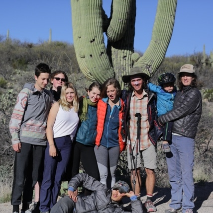 Group of hikers standing infront of a saguaro cactus