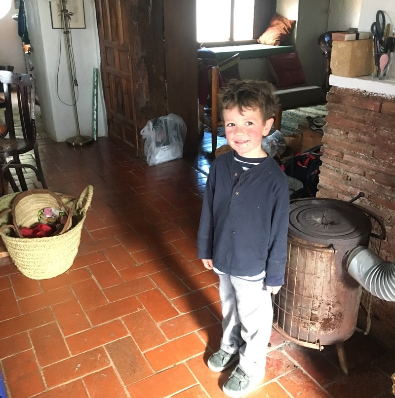 A young boy smiles in his home, standing in front of a stove
