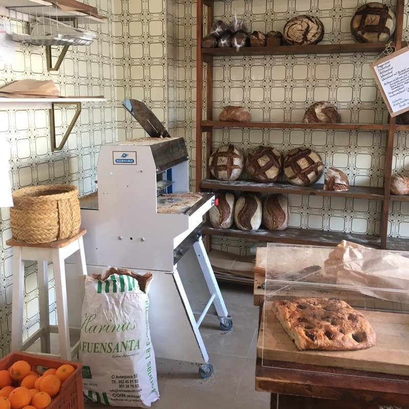 A bakery in Spain with thick rustic loaves on display, pasteries, and a case of oranges