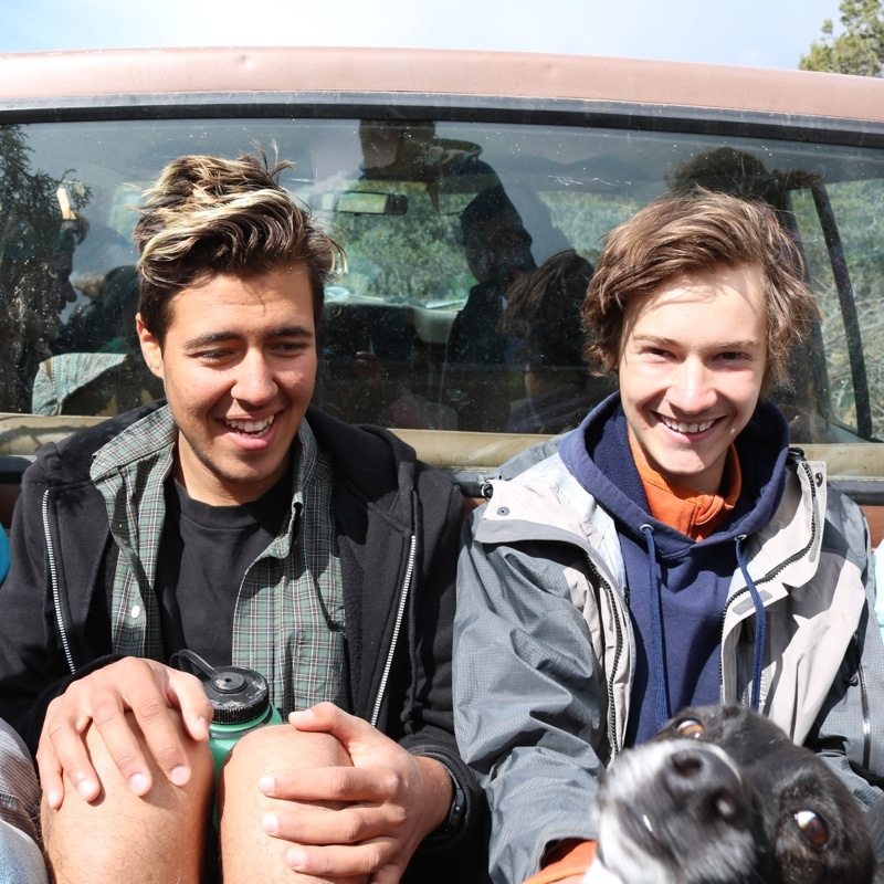 two young men smiling in the back of a pick-up truck