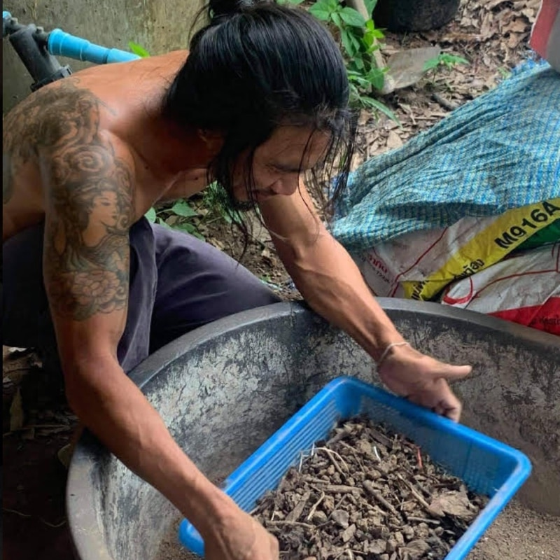 a Thai man with tatoos and no shirt sifts soil for a building project in buckets