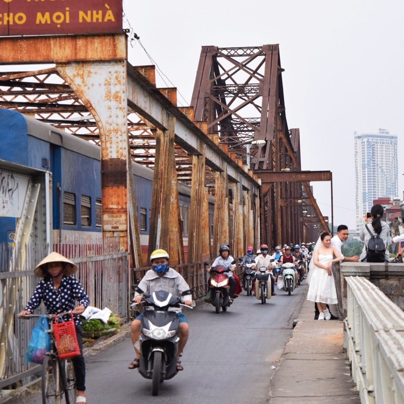 busy gritty street view of people on mopeds and with a woman in a wedding dress on the sidewalk talking to friends