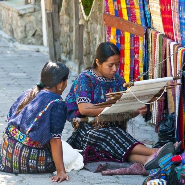 two women weaving on the street
