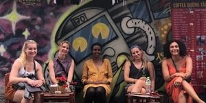 A group of young women share coffee in Thailand at an outdoor cafe decorated in graffiti