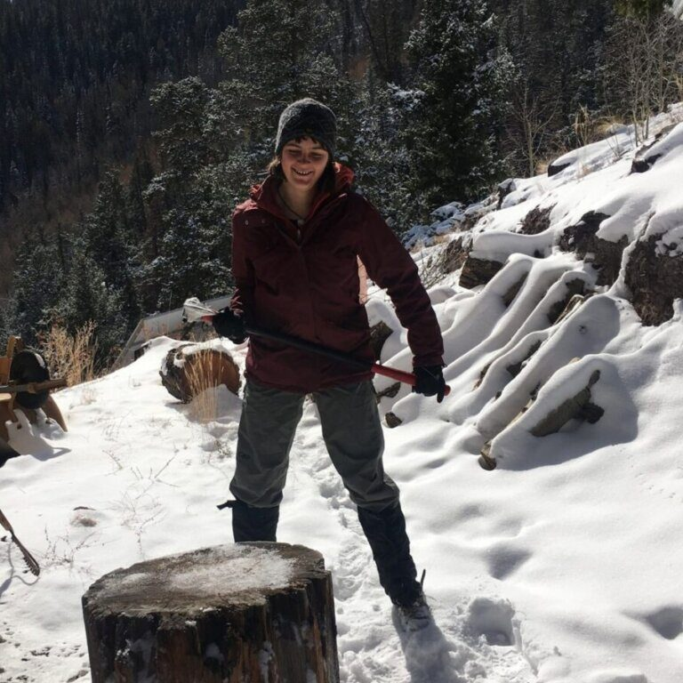 Gap year student chopping wood in the snow