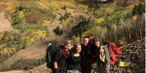 An outdoor gap year program adventure, four smiling teens are backpacking with mountains in the background.