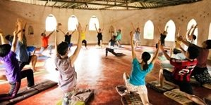 A group of people practice yoga in a circle in a round building made of natural materials