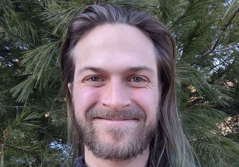 young man with long hair ad a beard smiling