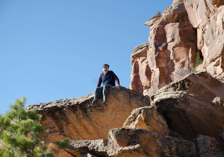 young man sitting on the edge of a boulder