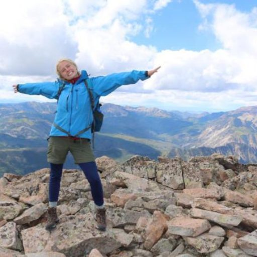 A teenager spreads her arms, celebrating on top of a mountain.