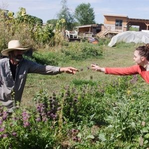 A young woman learning from a farmer outdoors in a garden.