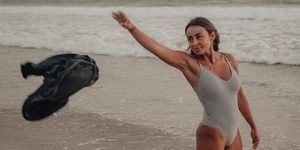 Young woman throws her shirt on the beach as she prepares to head into the ocean