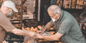 a man bags produce for a customer at a Spanish market
