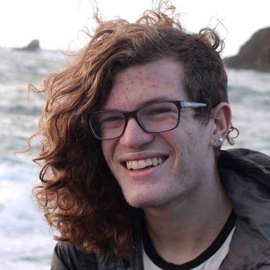 Young man with long curly hair smiling with ocean behind him