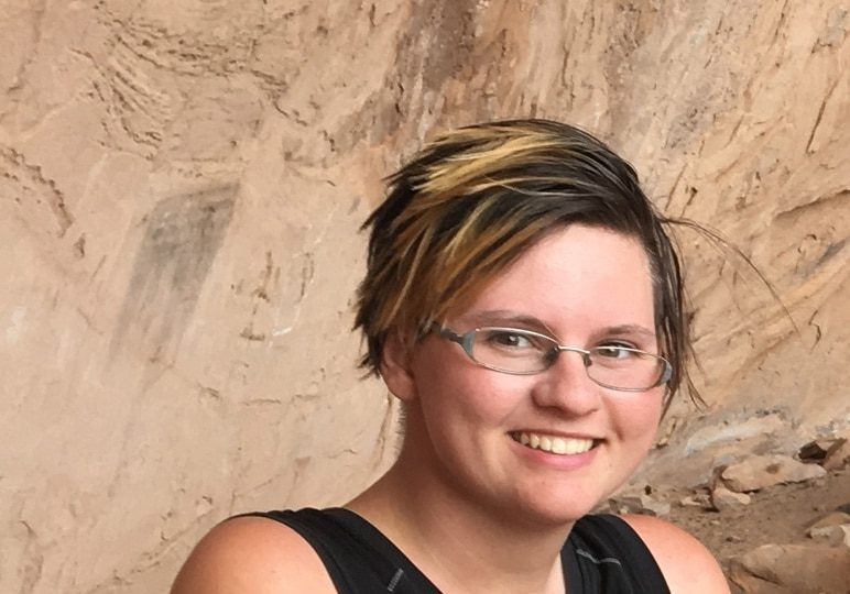 young person with short hair and glasses smiling
