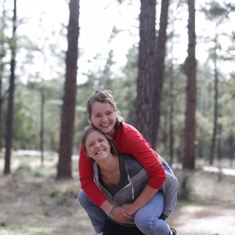 two young women, one on the other's back, smiling in the forest