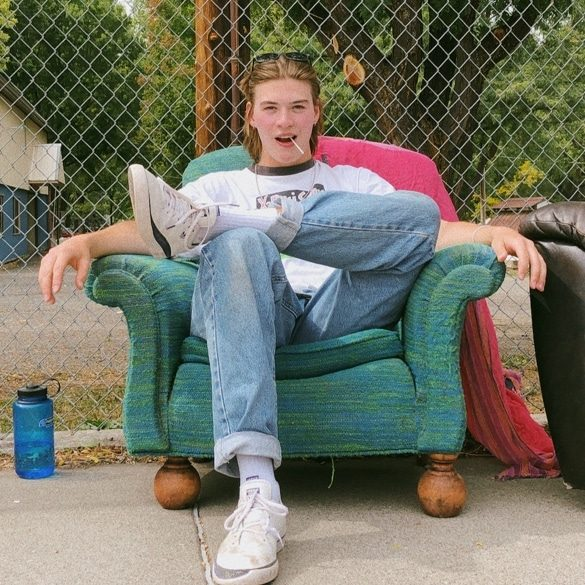 young man in a green chair outside
