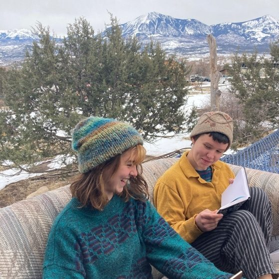 Two young women laugh over a piece of writing sitting outdoors with mountains as the backdrop